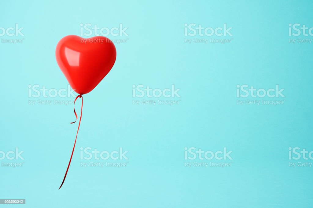 Red heart shape balloon against blue background stock photo