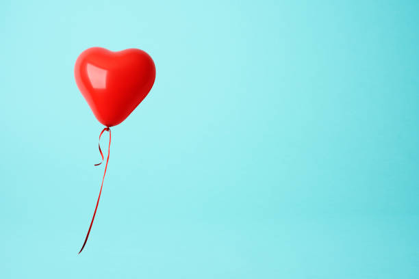 red heart shape balloon against blue background - conceptual symbol stock pictures, royalty-free photos & images