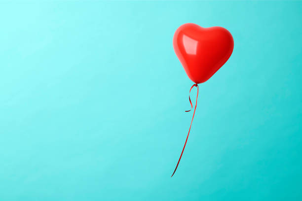 Red heart shape balloon in mid-air against blue background stock photo