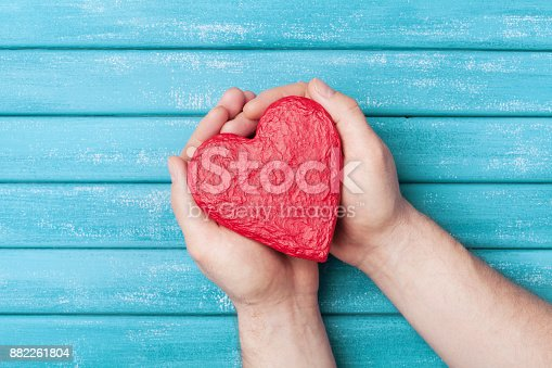 istock Red heart shape in hands top view. Healthy, donation organ, donor, hope and cardiology concept. Valentines day card. 882261804