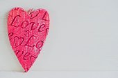 Red heart shape including the word love on white background