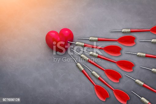 istock red heart shape object with red darts fly into on grey leather background 927656128