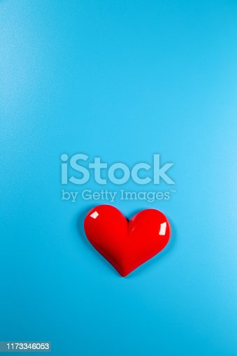 Red heart shape on blue paper background