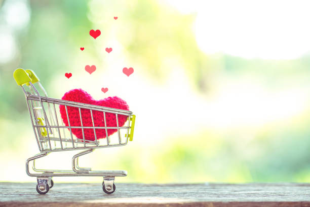 red heart shape on mini shopping cart over wooden background. Image for happy valentine day concept. stock photo