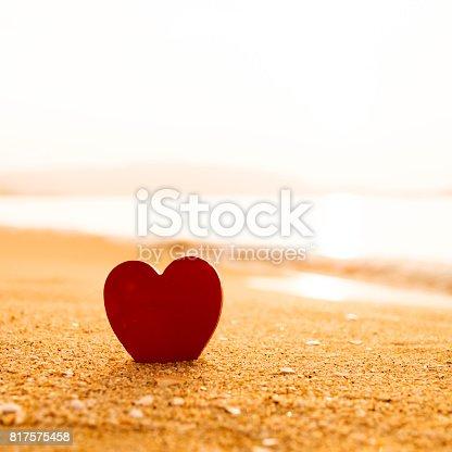 istock Red heart shape on the golden beach 817575458
