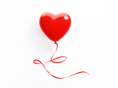 Red heart shaped balloon tied with red ribbon on white background. Isolated on white. Clipping path is included. Great use for love, romance and Valentine`s day related concepts.