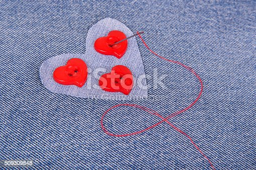 istock Red heart shaped buttons with needle and red thread 509309848