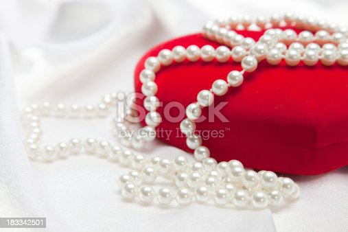 Red heart shaped jewelry box on white satin background