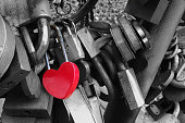 Red heart shaped padlock hangs on the bridge of lovers.  Concept - symbol of love and loyalty.