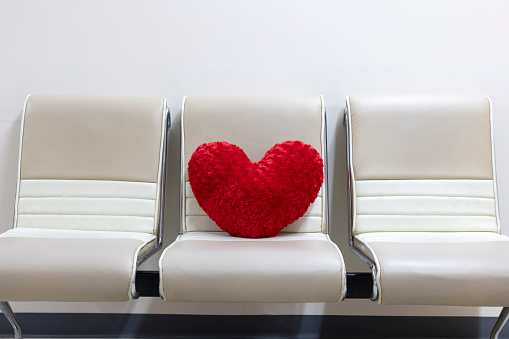 A red heart shaped velvet pillow left on a leather chair.