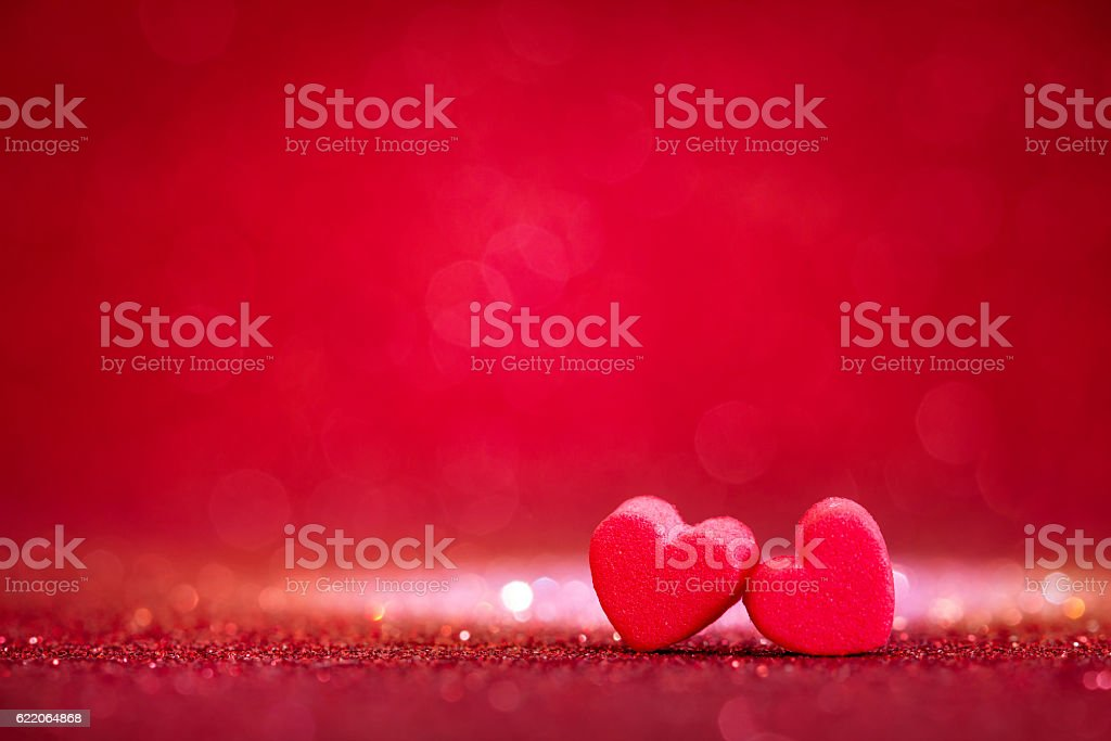 red Heart shapes on abstract light glitter background stock photo