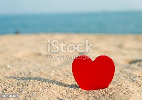 istock Red heart stuck in sand overlooking the ocean 467640075