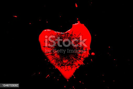 istock Red heart symbol broken into small splinters of glass from a shot from a pistol with a hole from a bullet isolated on a black background. Allegory of the unhappy love of a broken heart. 1046703052