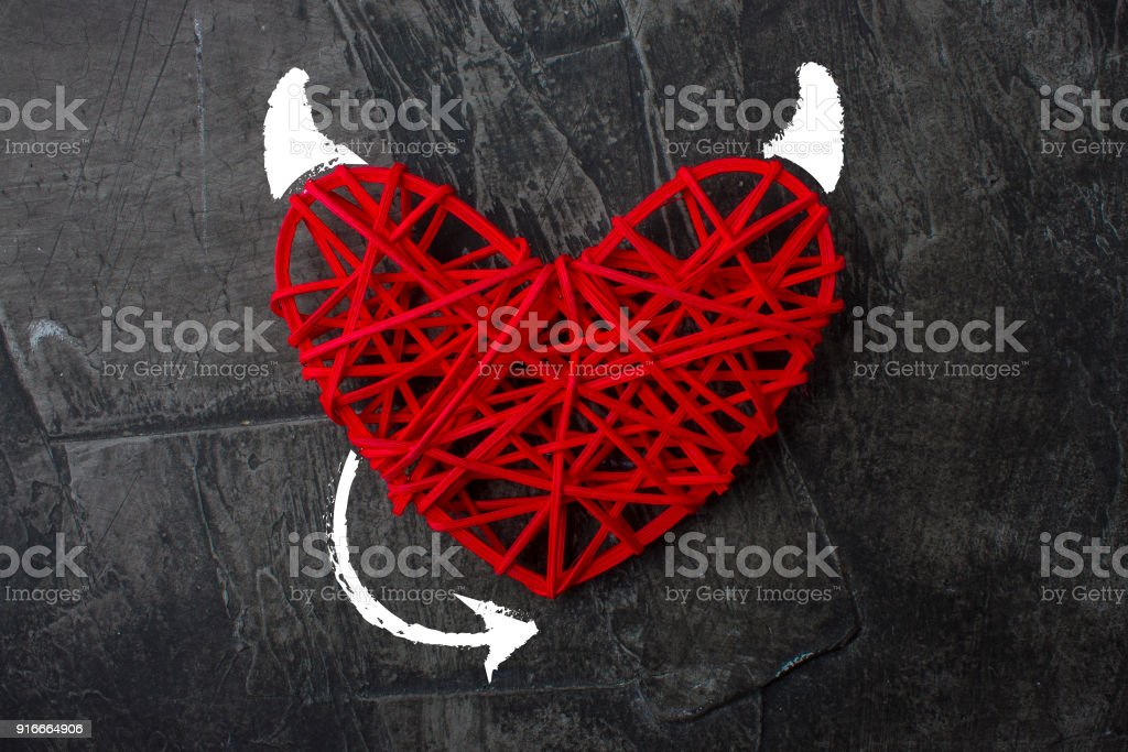 Red heart with a horn and tail of the devil Theme for Valentine's Day. Wedding, love stock photo