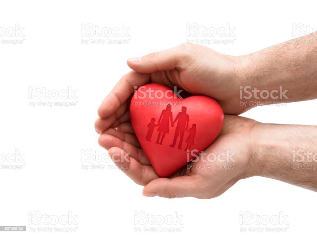 Red heart with imprinted family shape in man's hands. stock photo