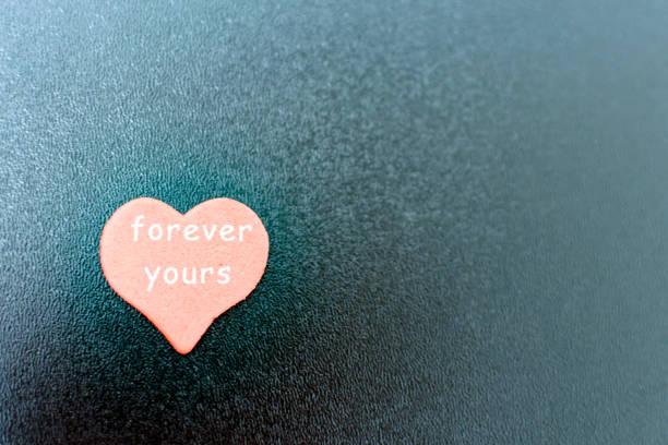 rotes Herz mit Inschrift am schwarzen Brett – Foto