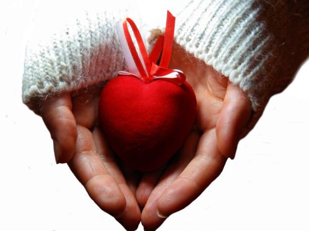 Beyaz baclkground üzerinde kadın elleri kırmızı ve beyaz çizgiler ile kırmızı kalp stok fotoğrafı