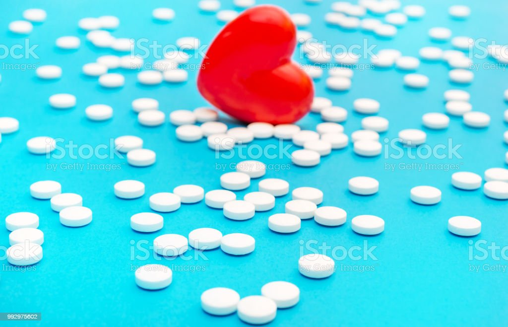 Red heart with white pills on blue. Medical background.