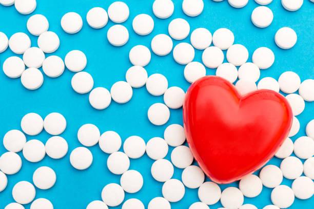 mavi üzerinde beyaz hapları olan kırmızı kalp. tıbbi arka plan. üst görünüm. metin alanı. - aspirin stok fotoğraflar ve resimler
