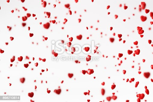 Red hearts falling over white background, Horizontal composition with selective focus.