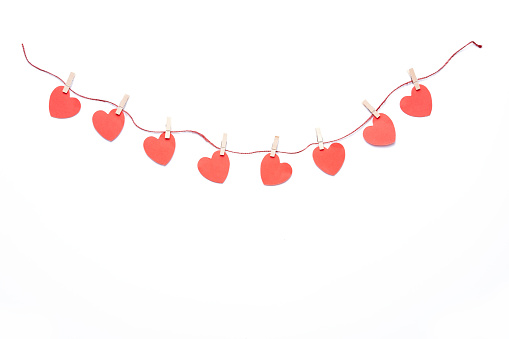 Red hearts garland hanging on white background