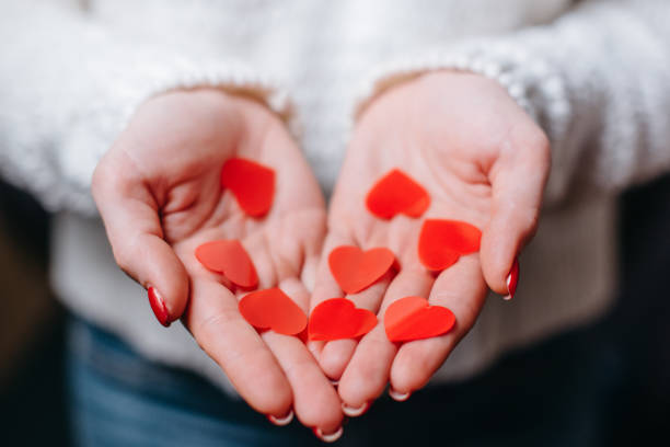 Red hearts in the palms of a woman, closeup. stock photo