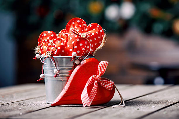 red hearts in zinc bucket on wooden background in vintage - senior valentine stock photos and pictures