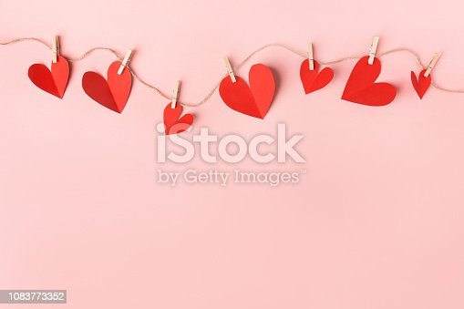 istock Red hearts on pink background 1083773352