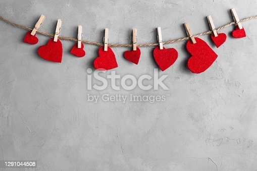 Red hearts on rope with clothespins, on a white grey concrete background. Place for text, copy space.
