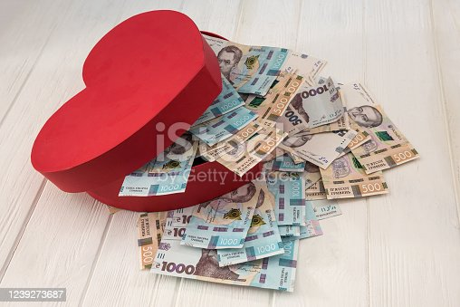 A red heart-shaped box full of money. UAH Money of Ukraine 1000 and 500 banknotes on deskv