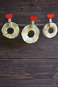 Red heart-shaped clothespins contain fruit chips. Dried organic apple fitness chips on a dark background. A popular tasty and fresh healthy product. A healthy, dietary, low-calorie and tasty snack.
