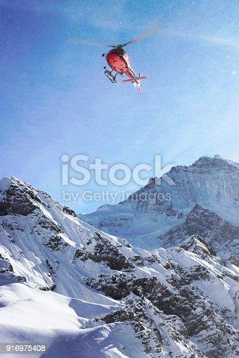 Red helicopter flying above Swiss Alpine mountain Mannlichen in winter, Switzerland