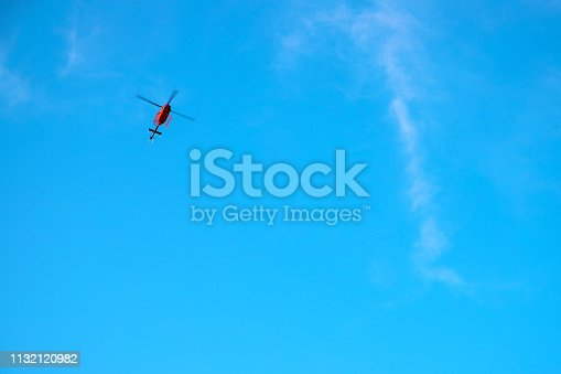 Red helicopter in blue sky. Emergency service helicopter flight. Red helicopter banner template with text place. Insurance or medical support concept. Sunny blue sky and special service flying vehicle