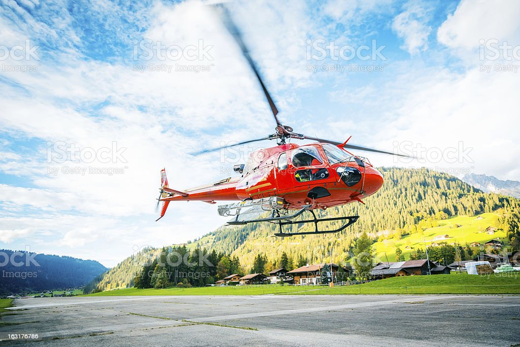 red helicopter in the swiss alps stock photo