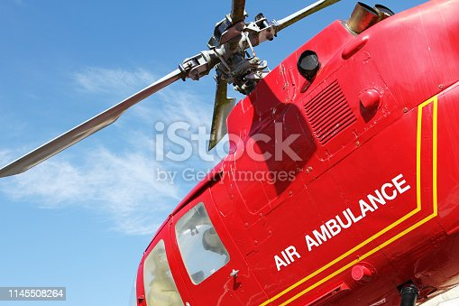 istock Red helicopter of air ambulance isolated on blue sky background. Detail of the helicopter blades. Cornwall, UK 1145508264