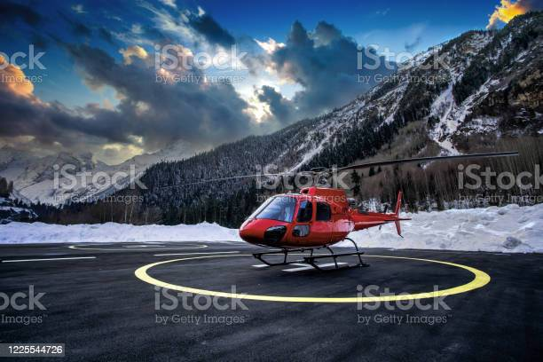 Photo of Red helicopter on the helipad at sunset.