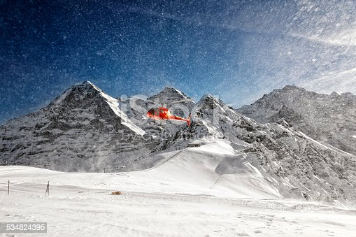 Red helicopter taking-off with snow powder clouds from swiss alpine resort