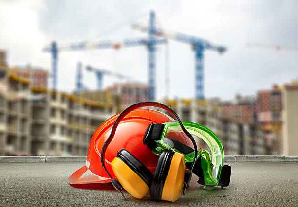 red helmet and earphones on buildings background - arbeidsveiligheid stockfoto's en -beelden