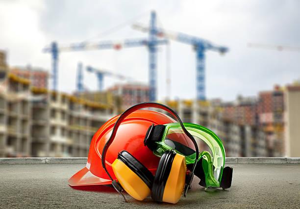 red helmet and earphones on buildings background - arbetssäkerhet bildbanksfoton och bilder