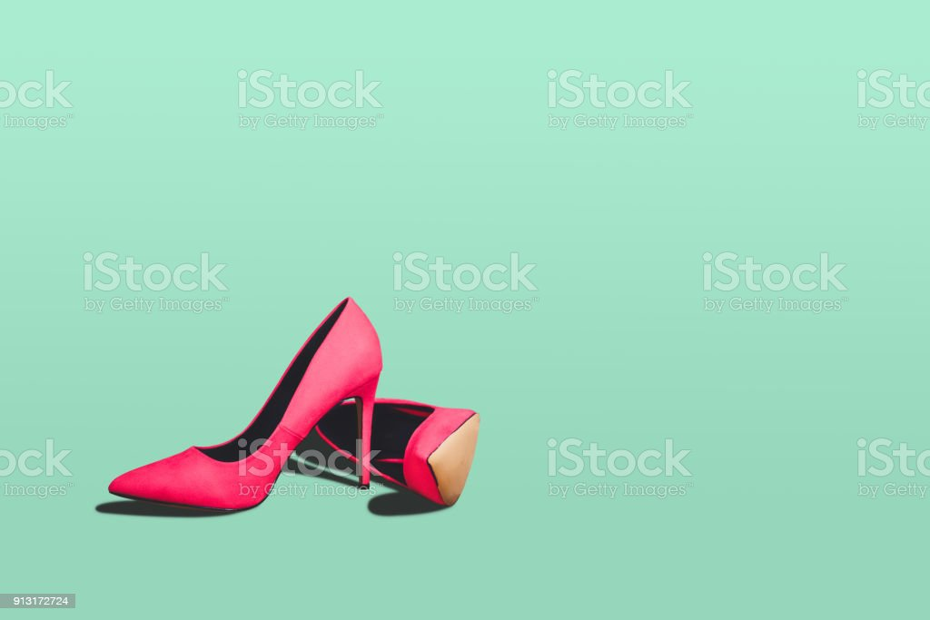 Red high heels isolated on a bright green pastel background. stock photo