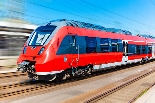 Red high-speed train with blurred motion Railroad travel and railway tourism transportation industrial concept: scenic summer view of modern high speed passenger commuter train on tracks with motion blur effect electric train stock pictures, royalty-free photos & images