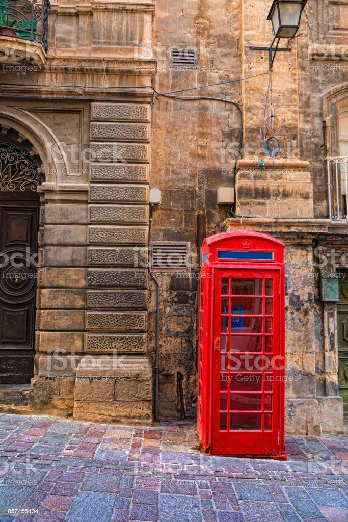 red historic telephone box in the street. Modern cardphone stock photo