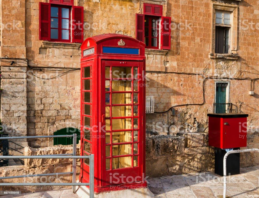 red historic telephone box in the street of Valetta - Malta. Modern cardphone stock photo