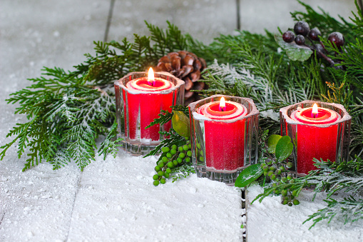 Three holiday candles burning by Christmas tree garland and snow