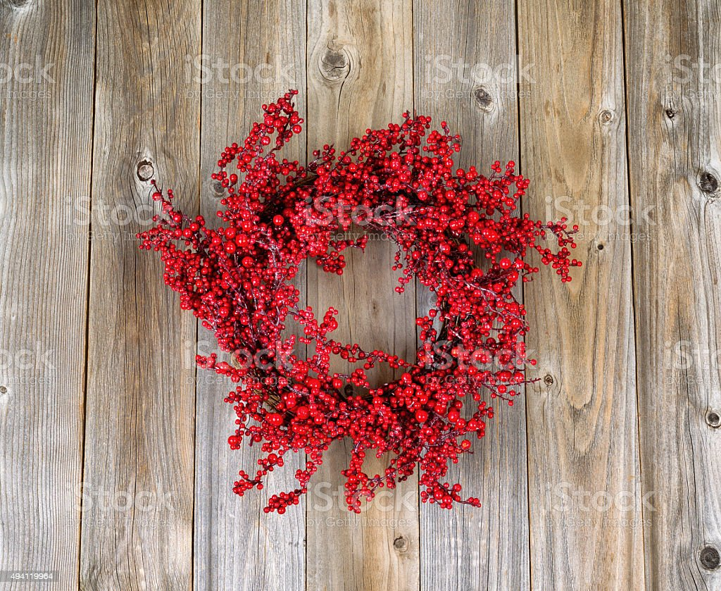 Red holly berry wreath on aged wooden boards stock photo