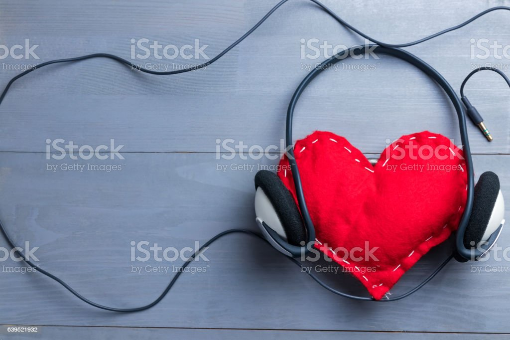 Red homemade heart with headphones on Valentine's Day. stock photo