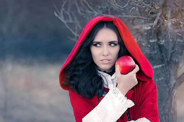 red hooded frau holding apple märchenhaften portrait - rotkäppchen kostüm stock-fotos und bilder
