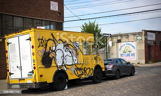 654490824 istock photo Red Hook, Brooklyn: Graffitied Truck on Cobbled Street 1054862582