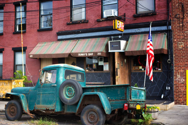 Red Hook, Brooklyn, NY: Vintage Willys Pickup Near Bar Red Hook, Brooklyn: An antique green Willys pickup truck flying a US flag and parked in front of an old-fashioned bar in Red Hook, Brooklyn, NY. willys stock pictures, royalty-free photos & images