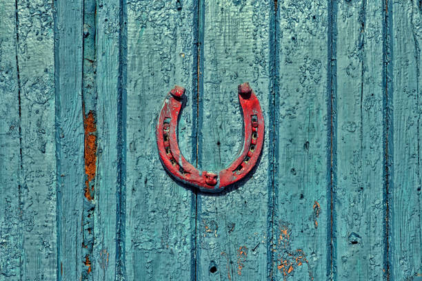 Red horseshoe hanging on an old wooden surface painted dark turquoise paint stock photo